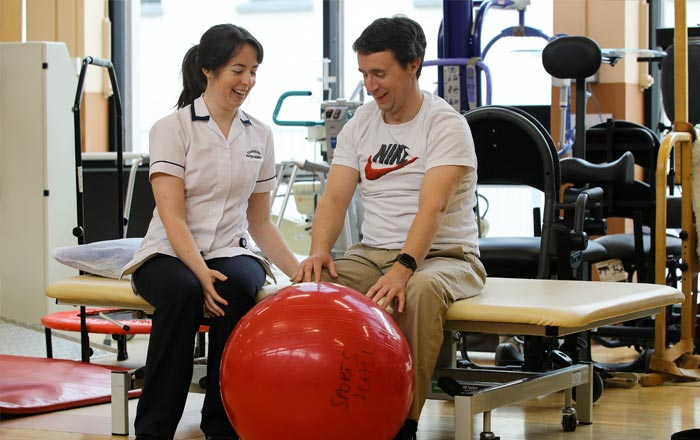 Female NRH staff member with male service user performing exercise with red yoga ball